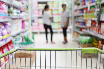 basket of Shopping trolley and blur supermarket background.