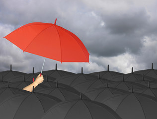 Red umbrella in hand and Surrounded by a black umbrella.