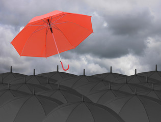 Red umbrella blown by wind and Surrounded by a black umbrella.