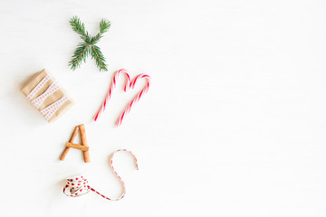 Christmas composition. Christmas candy canes, gift, cinnamon sticks and fir branches. Flat lay, top view