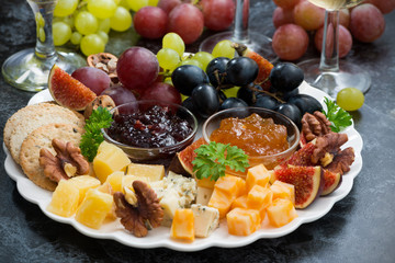 festive appetizers - cheeses, fruits and jams on plate