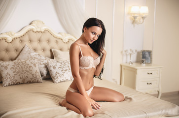 Beautiful girl in a sexy white lingerie on vintage bed