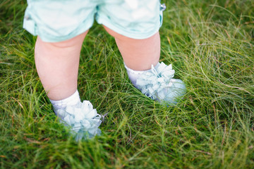 First steps of little girl in summer park on grass