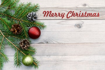 Christmas background on old wood. X-mas card with branch, red ball and cone. Copy space.