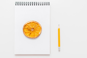 Dried lemon picture in notepad with pencil, free space. Sketchbook with citrus drawing and pencil on white background. Art, talent, artist concept