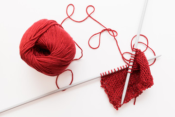 Red woolen thread and knitting needle isolated on white background. Sample of bordo knitted cloth with worktools. Handiwork, leisure, hobby concept