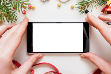 Hands holding smartphone with blank screen in frame of Christmas trumpery, mockup. Woman taking smartphone from festive table, white background