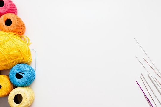 White background with knitting thread and needles, free space. Colorful strings and accessories for handiwork on white background, copy space for text or advertisement.