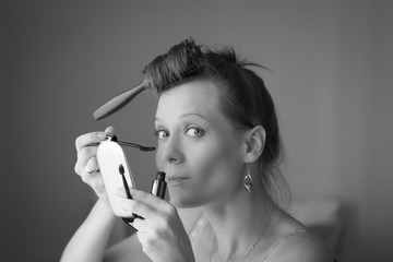 Beautiful woman applying make up.Processed in B&W.