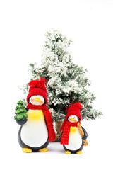Two penguin figurines with christmas tree in winter