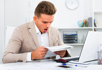 Upset  man having business problems with documents