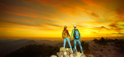 Two  hikers with backpacks enjoying sunset and view from the top of a mountain. Travel concept. Banner edition.