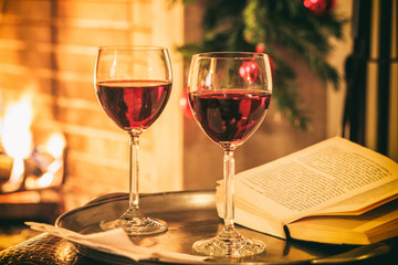 Two glasses of wine near a fireplace
