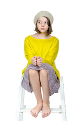 Barefoot girl sitting on a stepladder with a mysterious look..