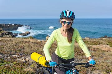 Portrait of tourist cyclists on a rocky ocean shore.