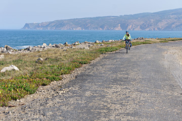 Happy female cyclist  rides a bicycle on the road along the ocean