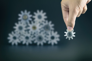 hand holding gears,on blurred  gears background, leadership concept , leading visionary