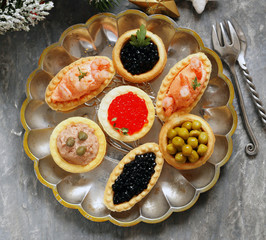 Christmas appetizers. Small tartlets with caviar and pate. Buffet and bar.