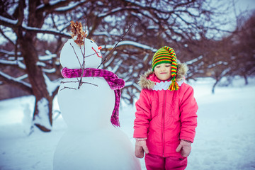 Little girl in the funny hat next to the snowman
