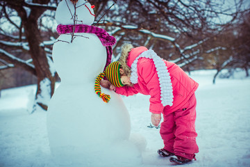 Cheerful girl next to the snowman with the scarf