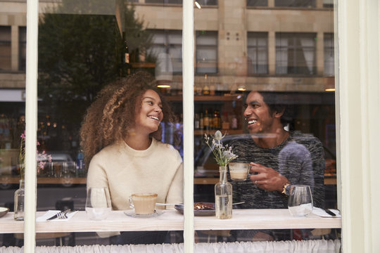 View Through Window Of Couple Enjoying Drink In Coffee Shop