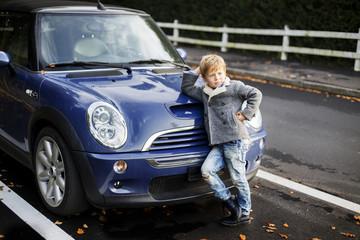 fashion kid boy stands near car