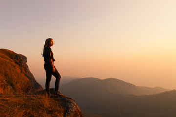 Hipster young girl with backpack enjoying sunset on peak of foggy mountain. Tourist traveler on background view mockup. Hiker looking sunlight in trip in Thailand country, mock up text.