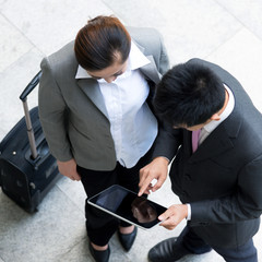 top view of woman and businessman with tablet and luggage