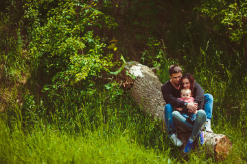 Happy young family sits on the block among the grass