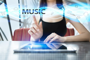 Woman is using tablet pc, pressing on virtual screen and selecting music