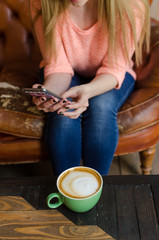 Young woman with coffee and phone