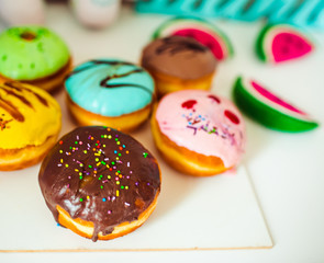 Donuts covered with colorful glaze lie on the table
