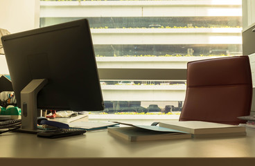 Work desk in office by the window with sun flare