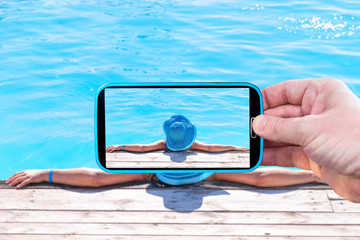 Making photos by smartphone of the girl in swimming pool