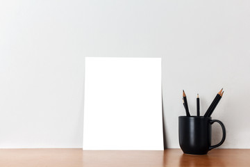 Blank white paper with pencils on a wooden desk