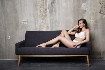 Lingerie girl relaxing on sofa, smiling