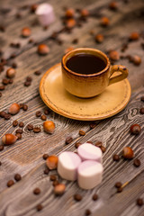 Small cup of coffee with cocoa beans, hazelnuts and marshmallow on wooden background