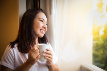Asian girl hold cup of coffee relaxing look outside window