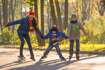 Three kids learning to ride in autumn park on rollerblades and s