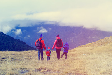 family with two kids hiking in winter mountains