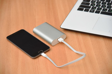 Smart phone and laptop with charger power bank on wood table.
