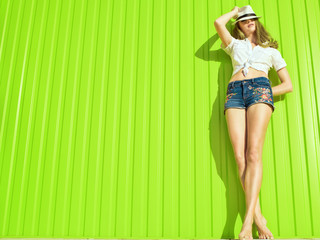 Portrait of young beautiful long-legged model in white tied up shirt, jeans shorts with flower ornament and panama on her eyes standing at the bright light green wall and relaxing. Copy-space