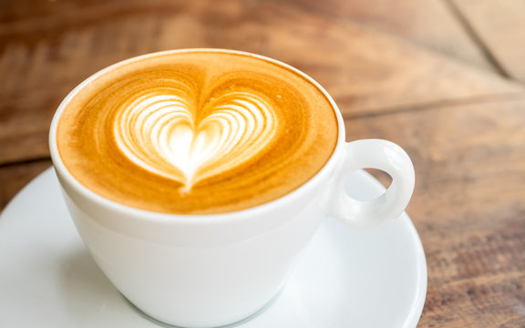 Close up white coffee cup with heart shape latte art on wood tab