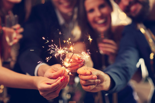 Group of friends having fun with sparklers