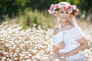 Summer portrait of a beautiful blonde woman with long straight hair,dressed in a light white sundress,on his head wearing a wreath of colorful flowers posing outdoors in flowery field