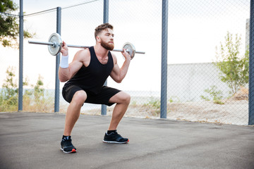 Concentrated bearded sports man doing squatting exercises with barbell