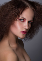 Beauty closeup portrait of young caucasian girl. Woman looking at camera. Beautiful fashion luxury makeup. Grey background.
