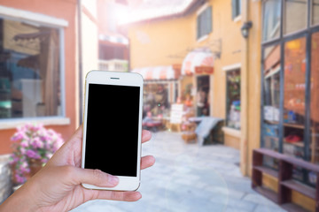Hands woman are holding touch screen smart phone,tablet on blurred street markets old building style background.