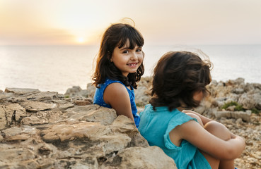 Portrait of happy little girl sitting with her sister near the sea at sunset