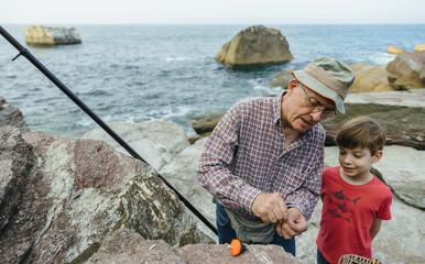Grandfather teaching grandson fishing at the sea